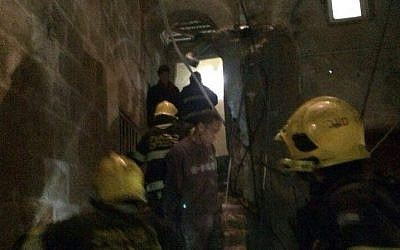 Firefighters attempt to reach people trapped inside a collapsed building in Acre after a gas explosion (photo credit: Ichud Hatzalah/Spokesman)