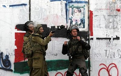 Israeli soldiers take position in front of the separation barrier on March 30, 2013 near the Qalandia checkpoint in the West Bank (photo credit: AFP/File Abbas Momani)
