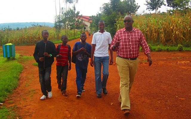 Jean-Claude Nkulikiyimfura, right, the director of the Agahozo-Shalom Youth Village, walking with students returning from lunch. (photo credit:  JTA/Ben Sales)