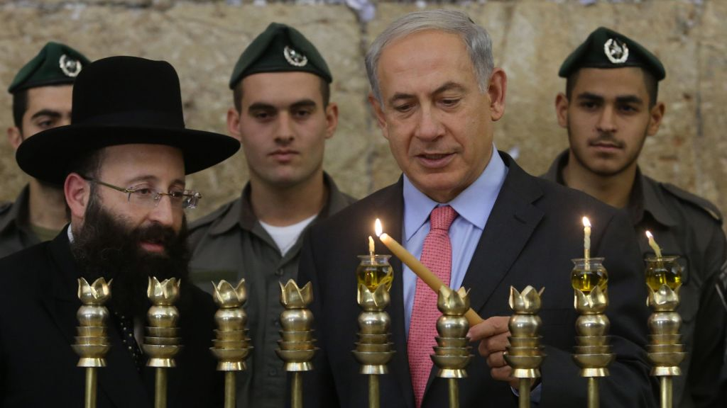 Prime Minister Benjamin Netanyahu lights the Hanukia together with Rabbi of the Western Wall Shmuel Rabinovitch, at the Western Wall on the second night of the Jewish holiday of Hannuka. November 28, 2013. (photo credit: Marc Israel Sellem/Pool/Flash90)