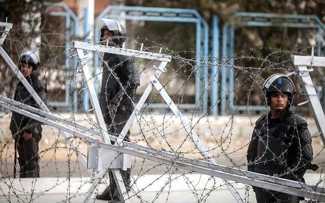 Egyptian riot police stand guard behind barbed wire outside the Police Academy in Cairo where a second hearing in the murder trial of deposed president Mohamed Morsi is expected to open on February 1, 2014 . (photo credit:  AFP/Mahmoud Khaled)
