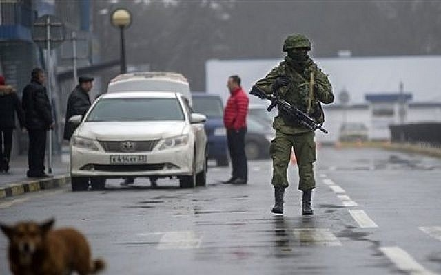 An unidentified armed man patrols a square in front of the airport in Simferopol, Ukraine, Friday, February 28, 2014. (photo credit: AP/Andrew Lubimov)