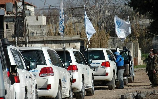 United Nations staff drive to the besieged district of the central Syrian city of Homs to help evacuate civilians to a safer location on February 9, 2014 (photo credit: AFP)