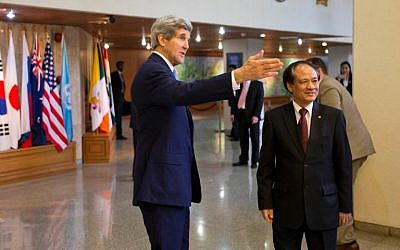 US Secretary of State John Kerry (L) introduces his staff before a meeting with ASEAN Secretary-General Le Luong Minh in Jakarta on Sunday, February 16, 2014 (photo credit: AFP/Evan Vucci)