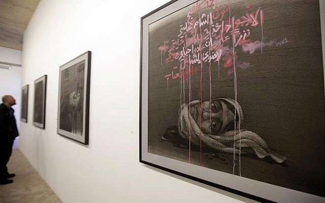 A picture taken on February 6, 2014 shows a man looking at paintings of Syrian artist Youssef Abdelke displayed at an art gallery in Beirut (Photo credit: AFP/Joseph Eid)