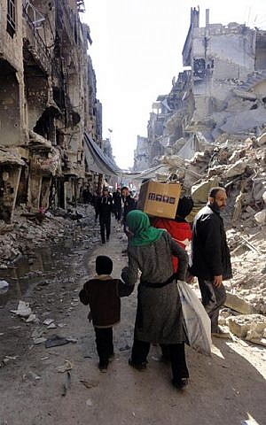 Residents of Syria's besieged Yarmouk Palestinian refugee camp carry food parcels, February 1, 2014 (photo credit: UNRWA/AFP)