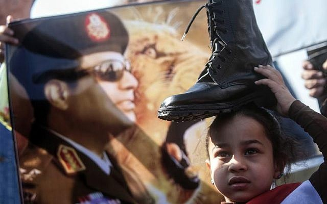 A supporter of Egypt's army chief Field Marshal Abdel Fattah al-Sisi (portrait) holds a military boot on her head at a demonstration outside the Police Academy in Cairo where a trial of deposed president Mohamed Morsi opened on January 28, 2014. (AFP/File/Mahmud Khaled)