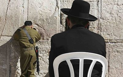 Could these two be in the same unit? In this illustrative photo of an Israeli soldier and ultra-Orthodox man pray at the Western Wall on February 2. (photo credit: Nati Shohat/FLASH90)