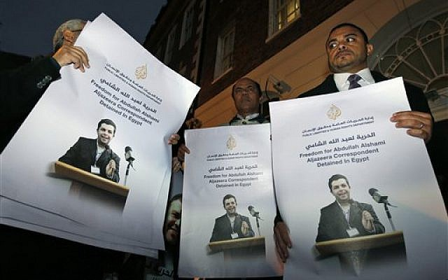 In this Tuesday, Nov. 12, 2013 file photo, demonstrators hold placards with pictures of Al-Jazeera Arabic network journalist Abdullah Al Shami who along with cameraman Mohamed Badr remain in custody in Egypt, during a protest calling for their release, outside Egypt's embassy in London. (photo credit: (AP/Lefteris Pitarakis, File)