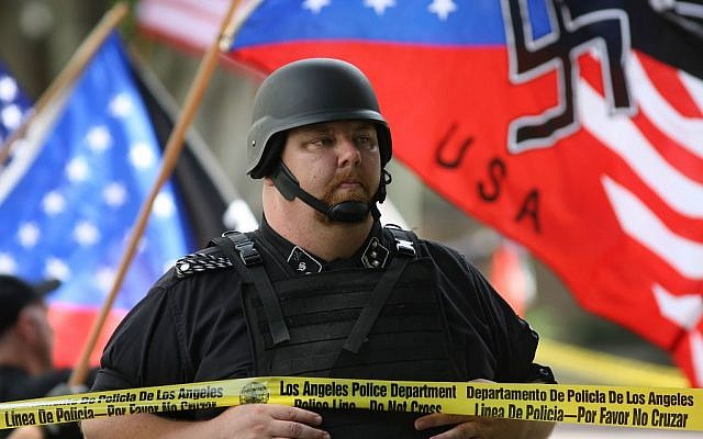 A member of the National Socialist Movement stands behind police tape line during a rally near Los Angeles City Hall on April 17, 2010. (David McNew/Getty Images/JTA)