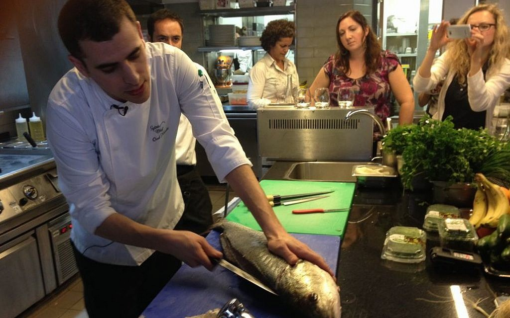 Chef Orel Kimchi demonstrates how to fillet a fresh sea bream (photo credit: Jessica Steinberg/Times of Israel)