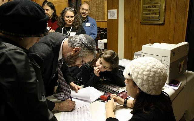 Rabbi Moshe Shulman of Young Israel of St Louis, signs the postnup with his wife, Baila Shulman. (photo credit: JTA/Rori Picker Neiss)
