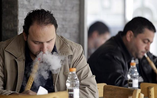 Men smoke traditional water pipes at an outdoor cafe in the Jordanian capital Amman on February 3, 2014. (photo credit: AFP/Khalil Mazraawi)