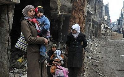 Residents of the besieged Yarmouk Palestinian refugee camp wait to leave the camp, on the southern edge of the Syrian capital Damascus, Syria, Feb. 4, 2014 (photo credit: AP/SANA)