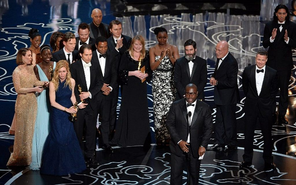 Director Steve McQueen (C) accepts the Best Picture award for '12 Years a Slave' with (back row) actors Sarah Paulson, Benedict Cumberbatch, Lupita Nyong'o, screenwriter John Ridley, actor Chiwetel Ejiofor, producers Arnon Milchan, Dede Gardner, Jeremy Kleiner and Anthony Katagas, actress Adepero Oduye and producer Brad Pitt onstage during the Oscars at the Dolby Theatre on March 2, 2014 in Hollywood, California. (Photo credit: AFP/Kevin Winter/Getty Images)