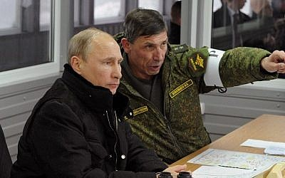 Russia's President Vladimir Putin (L) listens to the head of the Russian army's main department of combat preparation, Ivan Buvaltsev (R), while observing military exercises at the Kirillovsky firing ground in the Leningrad region, Monday, March 3, 2014. (photo credit: Mikhail Klimentyev/AFP)