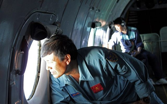Military personnel scanning the sea aboard a Vietnamese Air Force aircraft taking part in a search mission for a missing Malaysia Airlines aircraft, somewhere between Malaysia's east coast and southern Vietnam on Saturday. (photo credit: AFP/Thanh Nien Newspaper)