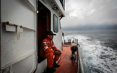 Indonesian national search and rescue agency personel watch over high seas during a search operation for missing Malaysia Airlines flight MH370 in the Andaman Sea on March 15, 2014 (Photo credit: Chaideer Mahyuddin /AFP)