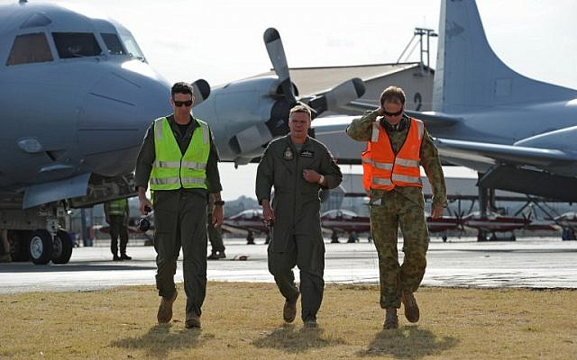 Royal Australian Airforce Flying Officer Peter Moore (C) walks to a media conference after returning his RAAF Orion plane to Pearce Air Force base in Bullsbrook, 35 kms north of Perth, after searching for missing Malaysia Airlines flight MH370 on March 22, 2014 (photo credit: AFP/Greg Wood)