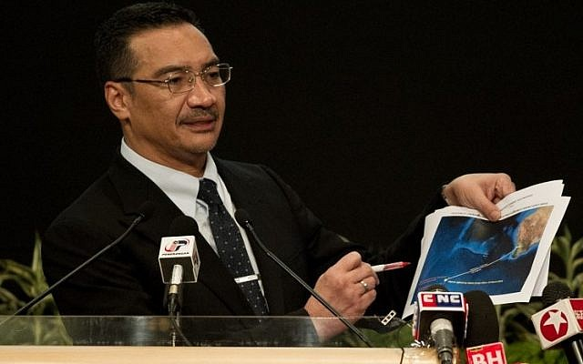 Malaysian Minister of Defense and Acting Transport Minister Hishammuddin Hussein shows pictures of possible debris during his statement on the missing Malaysia Airlines flight MH370 at the Putra World Trade Center (PWTC) in Kuala Lumpur on March 26, 2014. (photo credit: AFP Mohd Rasfan)