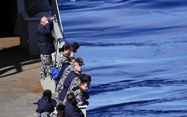 Crew members on the HMAS SUCCESS look for debris in the southern Indian Ocean during the search for missing Malaysia Airlines Flight MH370 on Wednesday March 26, 2014. (photo credit: Julianne Cropley/AFP)