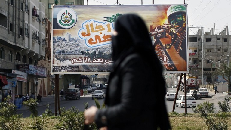 A Palestinian woman walks past a propaganda poster for the Hamas terrorist organization on March 5, 2014 in Gaza City, in the Gaza Strip (photo credit: AFP/Thomas Coex)