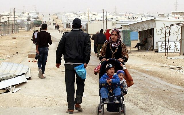 A Syrian refugee woman pushes a stroller at the Zaatari refugee camp, near the Jordanian border with Syria, on March 8, 2014. (AFP/Khalil Mazraawi)
