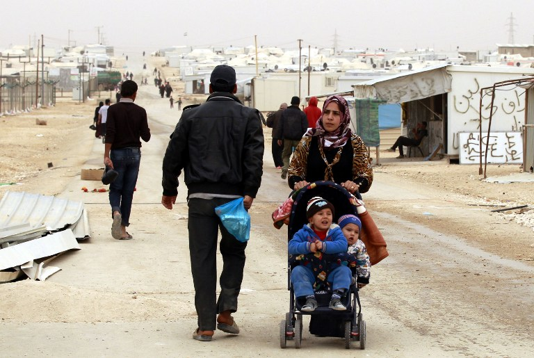 A Syrian refugee woman pushes a stroller at the Zaatari refugee camp, near the Jordanian border with Syria, on March 8, 2014. (photo credit: AFP/KHALIL MAZRAAWI)