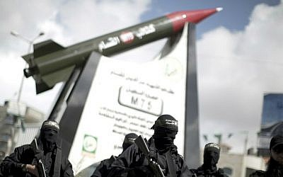 Members of theHamas's armed wing, stand in front of a model of a Gaza Strip-made M75 rocket newly displayed at the al-Jalaa square on March 10, 2014 in Gaza City. ( AFP photo/Mahmud Hams)