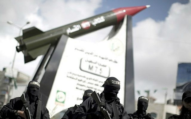 Members of the Izz ad-Din al-Qassam Brigades, Hamas's armed wing, stand in front of a model of a Gaza Strip-made M75 rocket newly displayed at the al-Jalaa square on March 10, 2014 in Gaza City. (photo credit: AFP photo/Mahmud Hams)