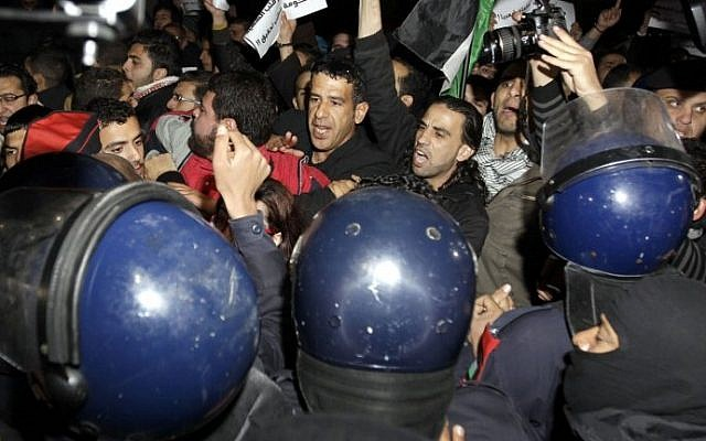 Riot police try to control several hundred angry Jordanians as they protest in front of the Israeli Embassy in Amman, Jordan, on Monday (photo credit: AFP/Khalil Mazraawi)