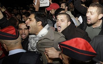 Riot police try to control angry Jordanians as they protest in front of the Israeli Embassy, demanding the ambassador's expulsion, in Amman, Jordan, on March 10, 2014. (photo credit: AFP/Khalil Mazraawi)