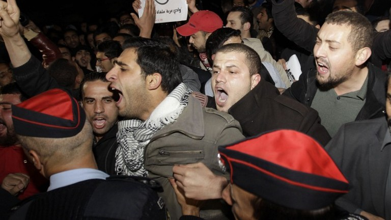 Riot police try to control several hundred angry Jordanians as they protest in front of the Israeli Embassy, demanding the ambassador's expulsion, in Amman, Jordan, on March 10, 2014. (photo credit: AFP/Khalil Mazraawi)