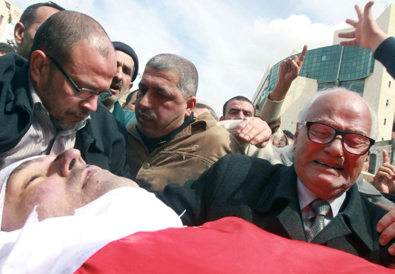The father of Raed Zeiter grieves over his son's body during his funeral in the northern West Bank city of Nablus, on March 11, 2014 (photo credit: AFP/Jaafar Ashtiyeh)