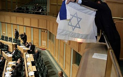 A Jordanian activist prepares to set a makeshift Israeli flag ablaze during a session of Jordan's House of Representatives on March 11, 2014 (photo credit: AFP PHOTO/STR)