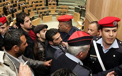 Security forces detain Jordanian activists who tried to set ablaze a makeshift Israeli flag during a session of Jordan's House of Representatives on March 11, 2014. (photo credit: AFP/STR)