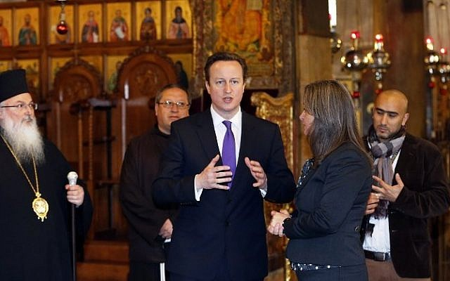 British Prime Minister David Cameron, center, talks to officials as he visits the Church of the Nativity in the West Bank town of Bethlehem, on March 13, 2014. (photo credit: AFP/POOL/THOMAS COEX)