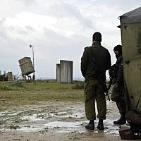 Illustrative: IDF soldiers stand near an Iron Dome missile defense battery, March 2014. (AFP/David Buimovitch)