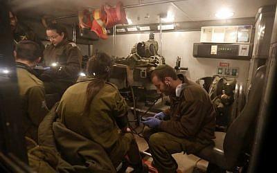 Israeli military medics examine comrades in an ambulance near Har Dov, on Israel's northern border with Lebanon, March 14, 2014 (photo credit: AFP/Jalaa Marey)