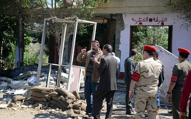 Egyptian soldiers and officials inspect the site where gunmen killed six soldiers at a Cairo checkpoint on March 15, 2014. (photo credit: AFP/AHMED GAMEL)