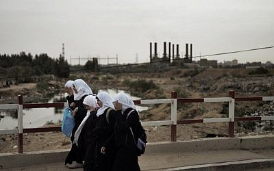 File photo of Palestinian school girls crossing a bridge over the garbage filled Wadi Gaza in the central Gaza Strip, as the silhouette of the Gaza Strip power plant is seen in the background. (Marco Longari/AFP)