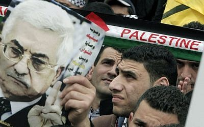 A man holds up an image of Palestinian Authority President Mahmoud Abbas as Palestinians rally in the center of the West Bank city of Nablus in support of Abbas during his visit to Washington, Monday, March 17, 2014. (photo credit: Jaafar/Ashtiyeh/AFP)