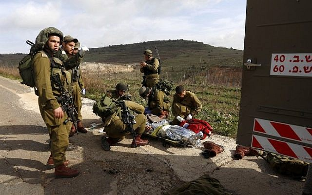 IDF soldiers prepare to evacuate a comrade injured in a blast on the border with Syria, near the village of Majdal Shams on Tuesday, March 18, 2014 (photo credit: AFP/Jalaa Marey)