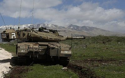 An Israeli army tank is seen stationed near the Golan Heights village of Majdal Shams, March 19, 2014. (AFP/Jalaa Marey/File)
