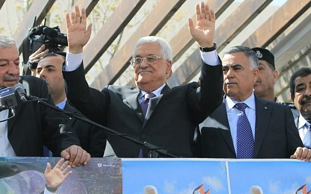 Palestinian Authority President Mahmoud Abbas waves to his supporters following his trip to Washington, DC, on Thursday, March 20, 2014, in the West Bank city of Ramallah (photo credit: AFP/Abbas Nomani)