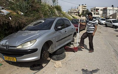 Illustrative: A Palestinian man changes the tires of his car after a 'price tag' attack in March 2014 (photo credit: AFP/Ahmad Gharabli)