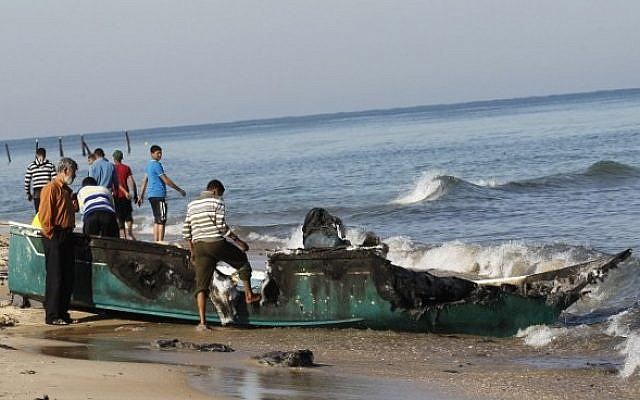 Palestinian fishermen inspect their destroyed fishing boat hauled up onto the shore, close to the southern Gaza Strip town of Rafah, on March 26, 2014. (Photo credit: Said Khatib/AFP)