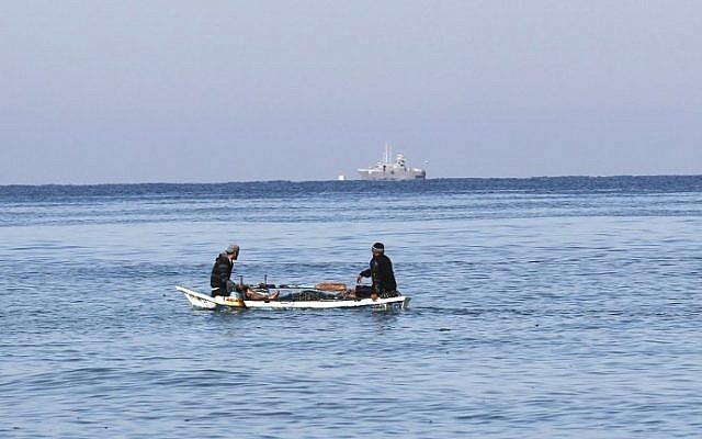 Palestinian fishermen sit in their boat off the shores of the southern Gaza Strip town of Rafah, as an Israeli patrol is seen in the distance, March 26, 2014. (AFP/Said Khatib)