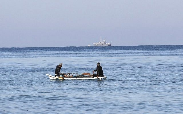 Palestinian fishermen sit in their boat off the shores of the southern Gaza Strip town of Rafah, as an Israeli police boat is seen in the distance, March 26, 2014. (photo credit: AFP/Said Khatib)