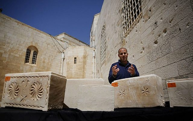 Israeli archaeologist Eitan Klein of the Antiquities Theft Prevention Unit stands next some of the 11 ancient coffins containing Jewish bones from the Second Temple period after they were recovered from thieves, on March 31, 2014 at the Rockefeller Museum in Jerusalem. (photo credit:AFP/GALI TIBBON)